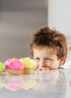 Siblings Peeking Over Counter At Row Of Cupcakes