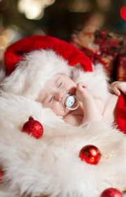 Christmas newborn baby sleeping in Santa Claus hat as new year gift